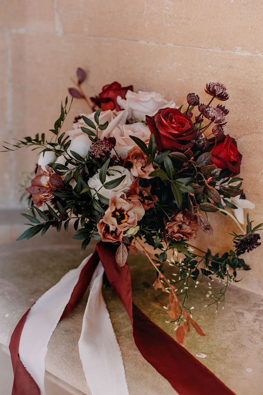 Bouquet of black baccara rose, astrantia, white ranunculus, jasmine and bohemian mocha lisianthus in Perfect Wedding Magazine